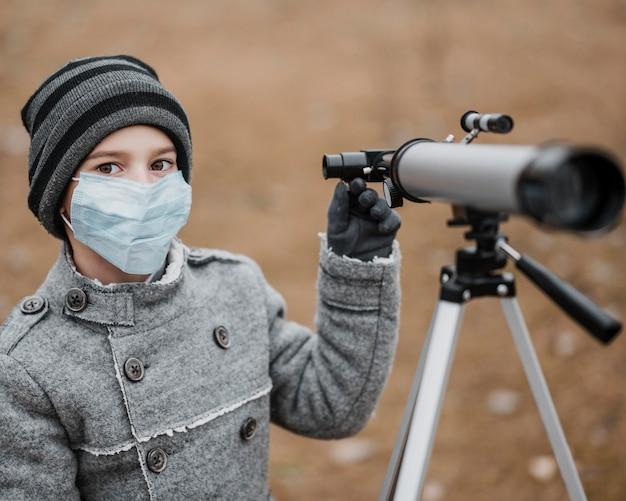 Vorderansicht kleiner junge mit medizinischer maske unter verwendung eines teleskops