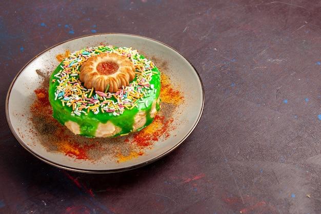 Vorderansicht kleiner köstlicher kuchen mit grüner sahne auf dunklem wandplätzchenkeks süßem zuckerkuchenkuchen