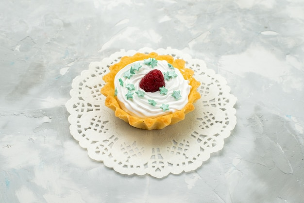 Vorderansicht kleiner köstlicher kuchen mit sahne-stern-bonbons und himbeere auf dem hellen schreibtischteig