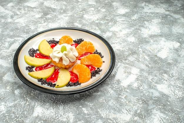 Vorderansicht kleiner kuchen mit geschnittenen äpfeln und mandarinen im teller auf weißem hintergrund süßer obstkuchen zuckerkeksplätzchen
