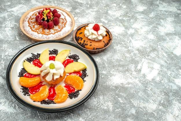 Vorderansicht kleiner kuchen mit geschnittenen früchten und kuchen auf weißem hintergrund süßer obstkuchen cookie zuckerkeks