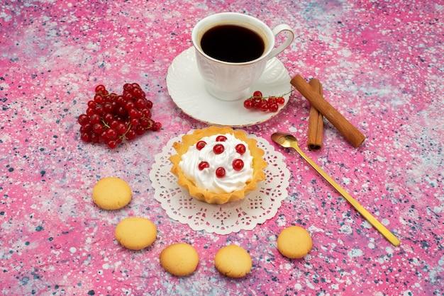 Vorderansicht kleiner kuchen mit sahnekeksen frische himbeeren zusammen mit tasse kaffee auf dem farbigen oberflächenkeks
