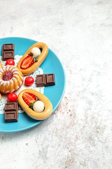 Vorderansicht kleiner kuchen mit süßer crackerschokolade und erdbeeren auf einem weißen hintergrund süßer kekskuchen-fruchtkekskuchen