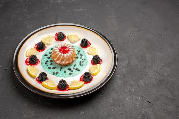 Vorderansicht kleiner leckerer kuchen mit konfitüren und zitronenscheiben im teller auf dunklem hintergrund obst zitruskekse keks süß