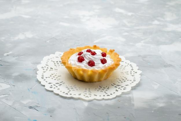 Vorderansicht kleiner leckerer kuchen mit sahne und roten früchten auf der hellen oberfläche