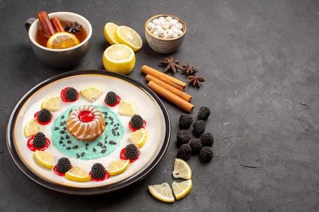 Vorderansicht kleiner leckerer kuchen mit zitronenscheiben und tasse tee auf dunklem hintergrund obst zitrus keks keks süß