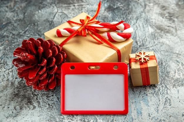 Vorderansicht kleines geschenk mit rotem band weihnachtsbonbonkartenhalter tannenzapfen auf grau gebunden