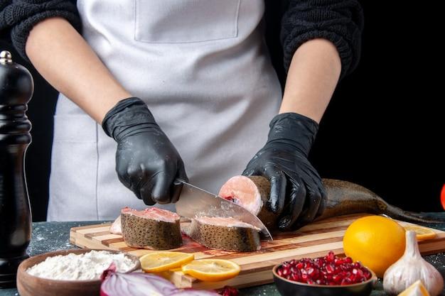 Vorderansicht-koch, der rohen fisch auf schneidebrettmehlschüssel auf tisch schneidet