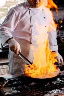 Vorderansicht koch, der rundes hackfleisch in der küche vorbereitet