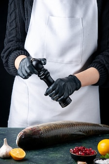 Vorderansicht koch in schürze bestreut pfeffer mit pfeffermühle auf frischen fisch granatapfelkernen in schüssel auf tisch