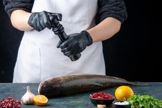 Vorderansicht koch in weißer schürze bestreut pfeffer mit pfeffermühle auf frischen fisch granatapfelkernen in schüssel auf tisch