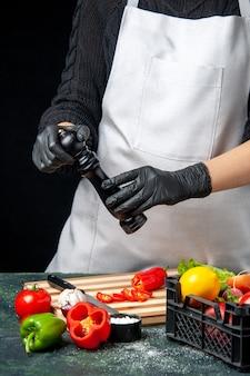 Vorderansicht köchin, die gemüse auf dunklen lebensmittelfarben würzt salatküche küche mahlzeit
