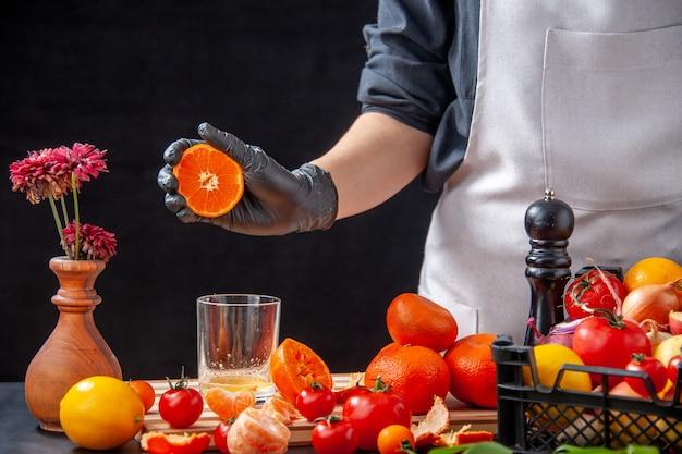 Vorderansicht köchin, die mandarinensaft auf dem schwarzen salat gesundheit mahlzeit lebensmittel job diät gemüse frisches getränk obst macht