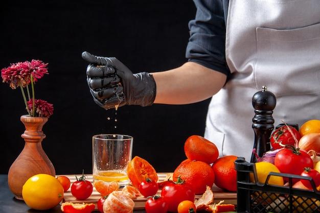 Vorderansicht köchin, die mandarinensaft auf einem schwarzen salat gesundheit mahlzeit lebensmittel job gemüse frische getränke obst diät macht