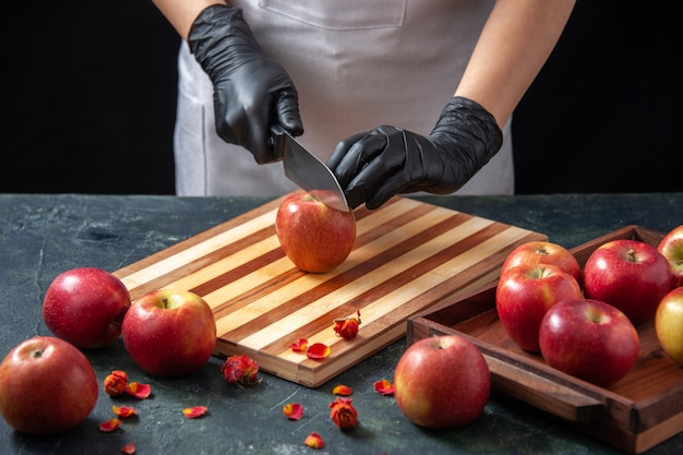 Vorderansicht köchin, die sich darauf vorbereitet, äpfel auf einem dunklen gemüsediätsalat zu schneiden, trinken essen zitrusfrüchte essen exotisch