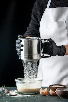Vorderansicht köchin gießen mehl in eier auf dunklem hotcake gebäck kuchen kuchen küche teig arbeiter Kostenlose Fotos