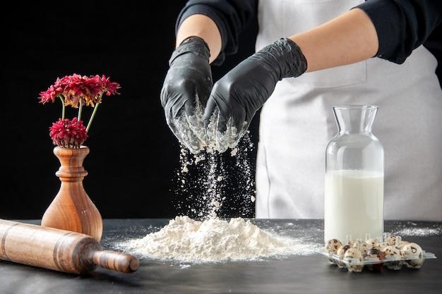 Vorderansicht köchin gießen weißmehl auf tisch für teig auf einem dunklen job gebäck kuchen bäckerei kochen teig backen kuchen keks