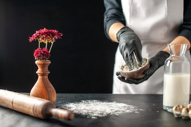 Vorderansicht köchin gießt weißes mehl auf den tisch für teig auf dunklem obst job gebäck kuchen kuchen bäckerei kochen