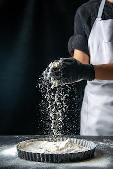Vorderansicht köchin gießt weißes mehl in die pfanne auf dunklem eierkuchen bäckerei gebäck küche kuchen hotcake küchenteig