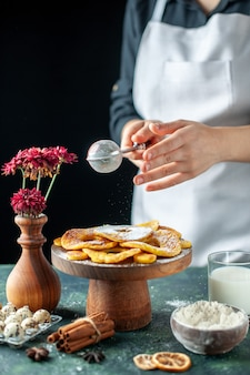 Vorderansicht köchin gießt zuckerpulver auf getrocknete ananasringe auf dunklem obst kochen job gebäck kuchen kuchen bäckerei