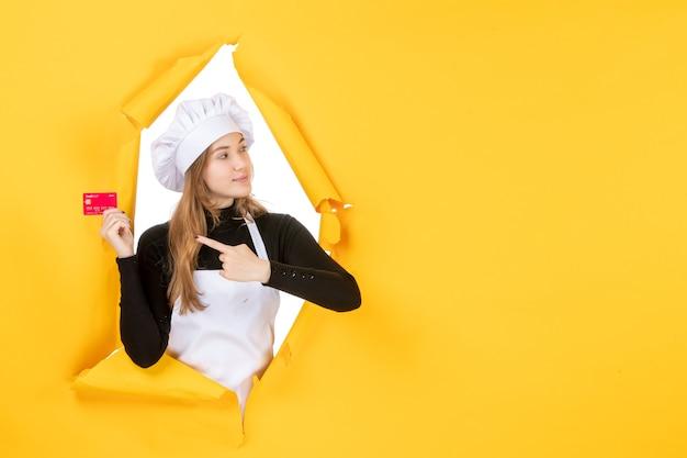 Vorderansicht köchin hält rote bankkarte auf gelbem geld farbe job foto küche küche emotion essen
