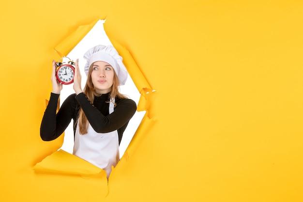 Vorderansicht köchin hält uhr auf gelbem lebensmittelfoto farbe job küche küche emotion zeit sonne