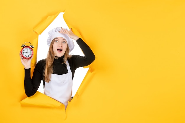 Vorderansicht köchin hält uhren auf gelber zeit essen foto job küche emotion sonne küche farben