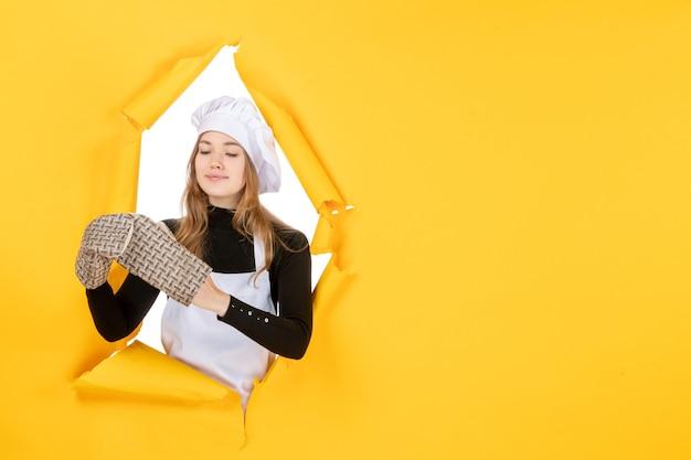 Vorderansicht köchin in kochhandschuhen und weißer kochmütze auf einem gelben sonnenlebensmittelfarbe-küche-emotion-küchen-jobfoto