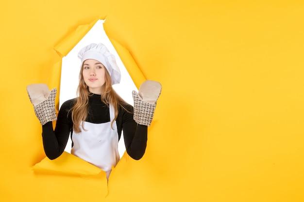 Vorderansicht köchin in kochhandschuhen und weißer kochmütze auf einem gelben sonnenlebensmittelfarbe-küchenfoto-emotions-küchenjob