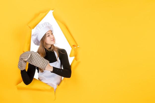 Vorderansicht köchin in kochhandschuhen und weißer kochmütze auf gelbem sonnenlebensmittelfarbe emotionsküchenjobfoto