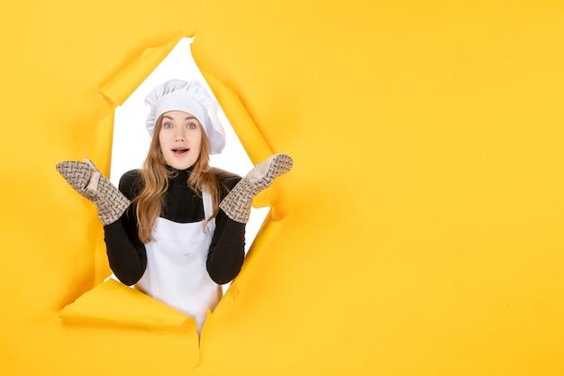 Vorderansicht köchin in kochhandschuhen und weißer kochmütze auf gelber emotion lebensmittelfarbe küche küchenjob foto sonne