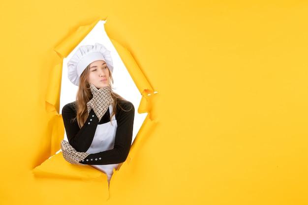 Vorderansicht köchin in kochhandschuhen und weißer kochmütze auf gelber lebensmittelfarbe küche foto emotion küchenjob
