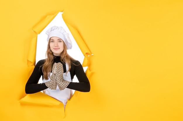 Vorderansicht köchin in kochhandschuhen und weißer kochmütze auf gelber sonne essen küche foto emotion küche job