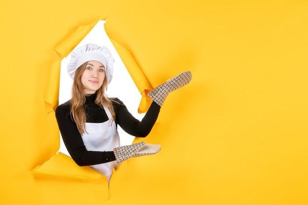 Vorderansicht köchin in kochhandschuhen und weißer kochmütze auf gelber sonne lebensmittelfarbe küche emotion küchenfoto