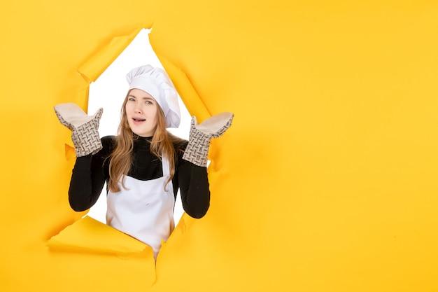 Vorderansicht köchin in kochhandschuhen und weißer kochmütze auf gelber sonne lebensmittelfarbe küche emotion küchenjob
