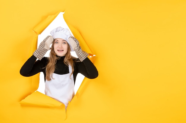 Vorderansicht köchin in kochhandschuhen und weißer kochmütze auf gelber sonne lebensmittelfarbe küche foto emotion küche