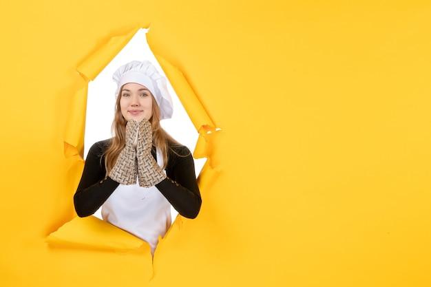 Vorderansicht köchin in kochhandschuhen und weißer kochmütze auf gelber sonne lebensmittelfarbe küche foto emotionen küche job
