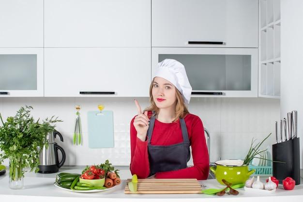 Vorderansicht köchin in uniform, die hinter dem küchentisch steht und auf den finger zeigt