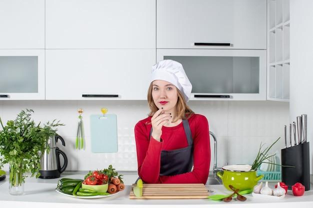 Vorderansicht köchin in uniform, die hinter dem küchentisch steht und die hand auf ihr kinn legt