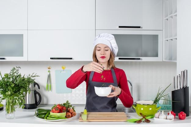 Vorderansicht köchin in uniform, die hinter dem küchentisch steht und eine schüssel mit grüns hält