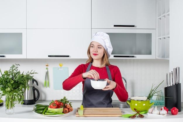 Vorderansicht köchin in uniform, die hinter dem küchentisch steht und etwas aus der schüssel nimmt