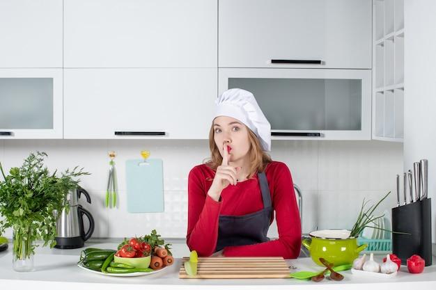Vorderansicht köchin in uniform, die hinter dem küchentisch steht und stillezeichen macht