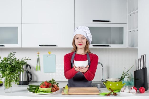 Vorderansicht köchin in uniform, die hinter küchentisch steht und weiße schüssel hält