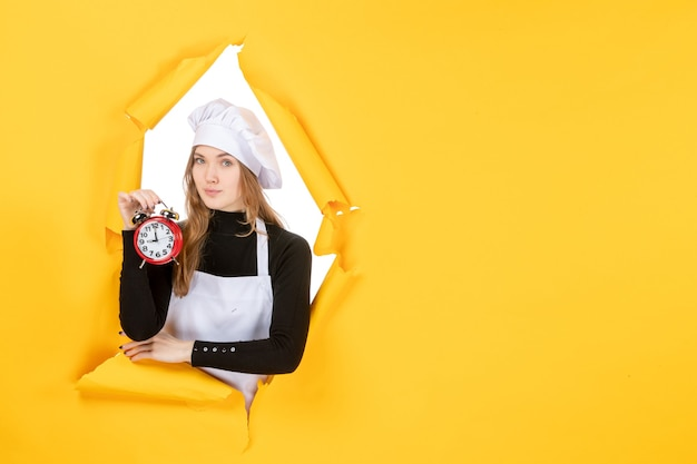 Vorderansicht köchin in weißer kochmütze mit uhr auf gelbem farbjob emotion essen küche küchenfoto