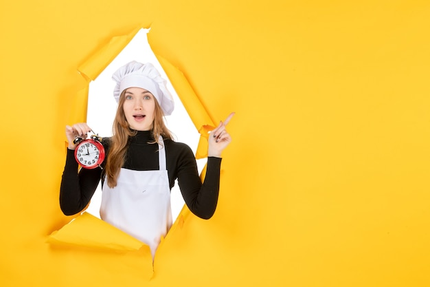 Vorderansicht köchin in weißer kochmütze mit uhr auf gelbem foto farbjob emotion küche küche sonne essen