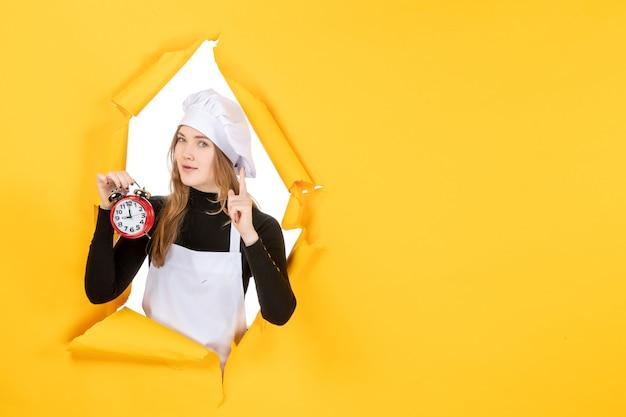 Vorderansicht köchin in weißer kochmütze mit uhr auf gelber farbe job emotion essen küche foto sonne