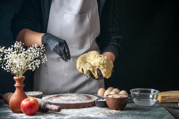 Vorderansicht köchin rollt teig auf dunklem job aus roher teigkuchen ofen gebäck hotcakes bäckerei ei