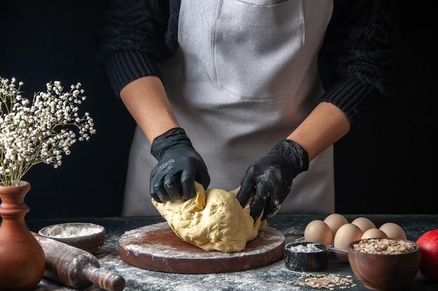 Vorderansicht köchin rollt teig auf dunklem job roher teig hotcake bakery pie ofen gebäck aus
