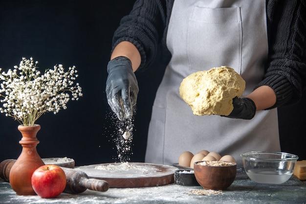 Vorderansicht köchin rollt teig mit mehl auf dem dunklen job teig gebäck küche hotcake küche bäckerei ei