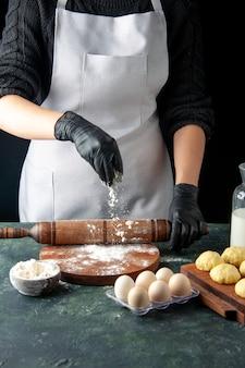 Vorderansicht köchin rollt teig mit mehl auf dunklem job küche hotcake raw bake cake pie arbeiter